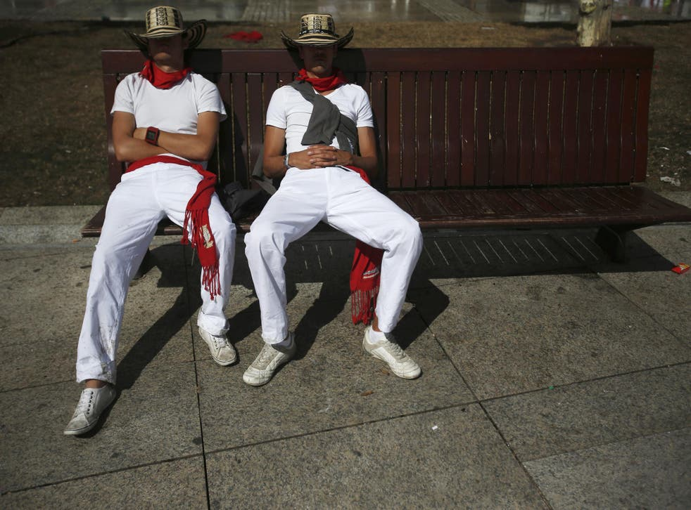 Revellers sleep on a bench after the second running of the bulls during the San Fermin festival in Pamplona