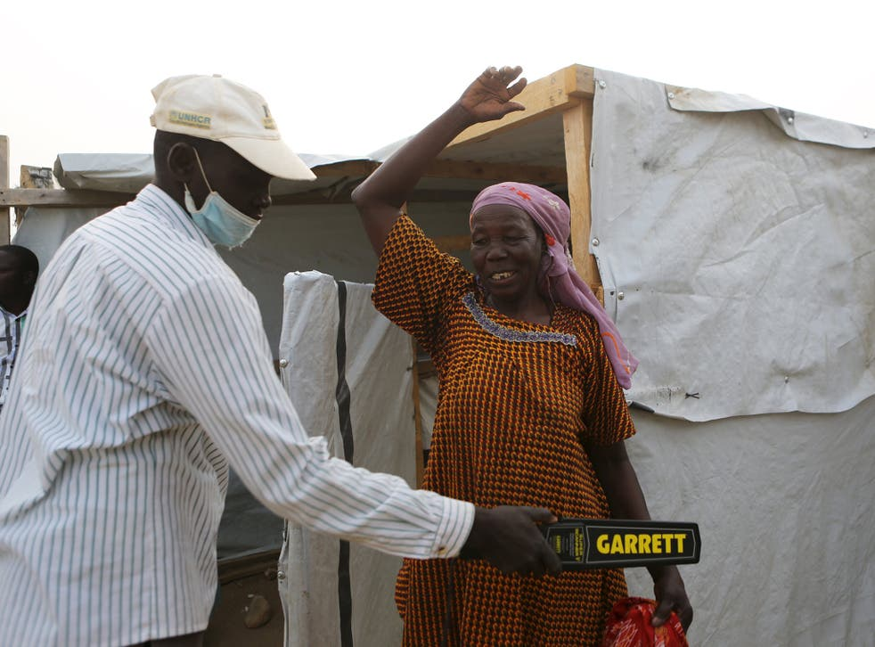 A security officer scans a woman entering a health clinic at Minawao refugee camp in Minawao
