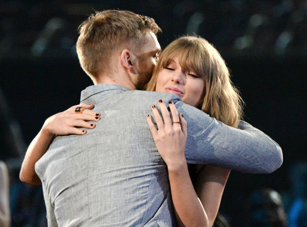 Calvin Harris and Taylor Swift hug during the iHeartRadio Music Awards