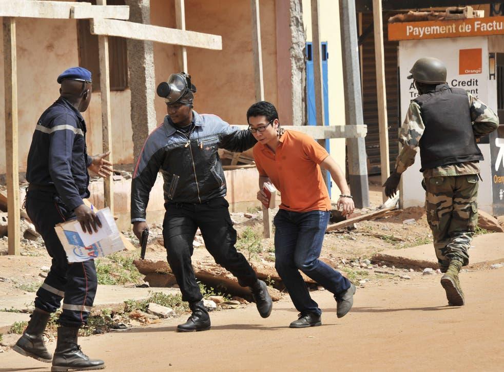 Malian security forces assist a man outside the Radisson Blu last November