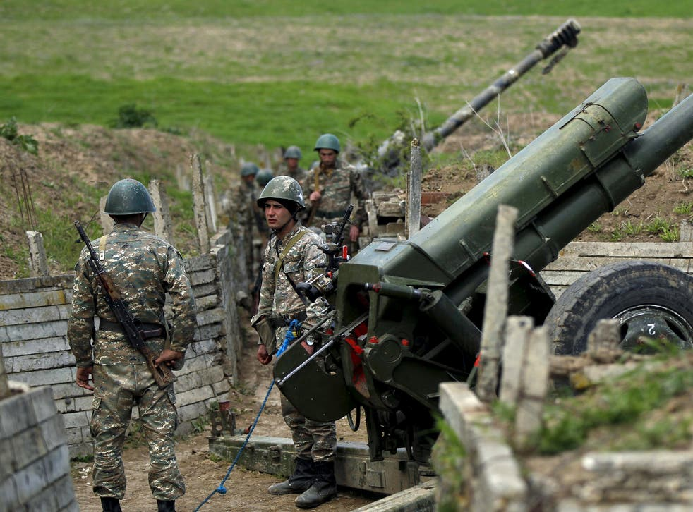 Ethnic Armenian soldiers stand next to a cannon at artillery positions near the Nagorno-Karabakh's town of Martuni