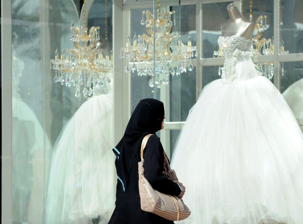 A Saudi woman walks past wedding dresses displayed in a shop window on February 4, 2013 at a mall in the Saudi capital Riyadh