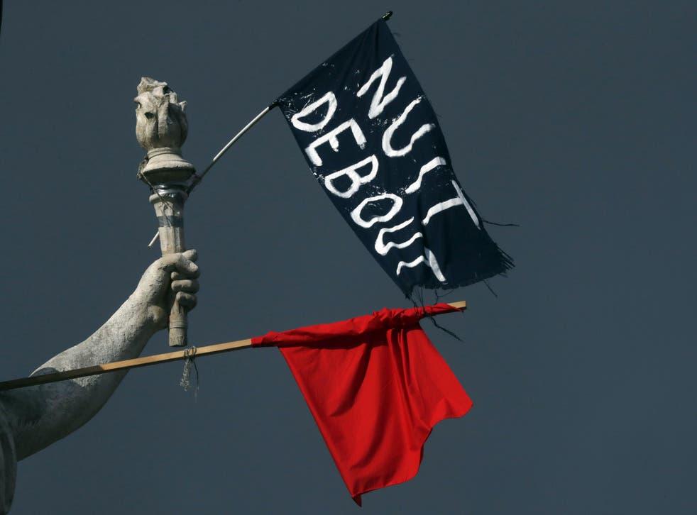 Flags of the 'Nuit Debout' movement hang off a statue in Place de la Republique in Paris