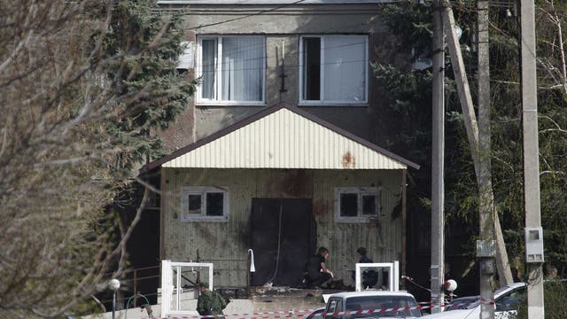 Investigators work near the entrance of a police station which was attacked in a settlement of the Novoselitsky district in Stavropol region