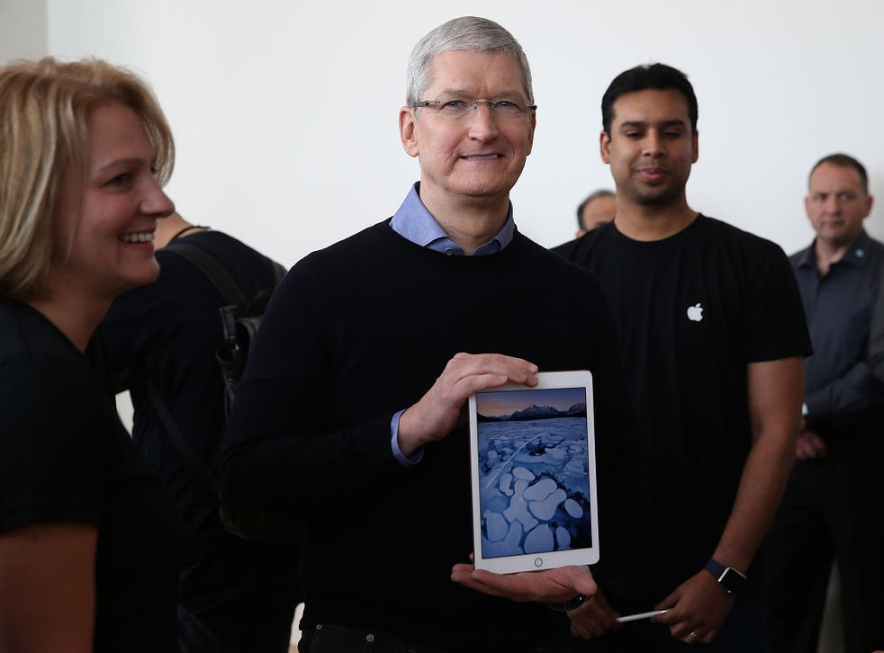 Apple CEO Tim Cook holding an iPad. The company expects users to replace their iPhone, iPad or Apple Watch device every three years