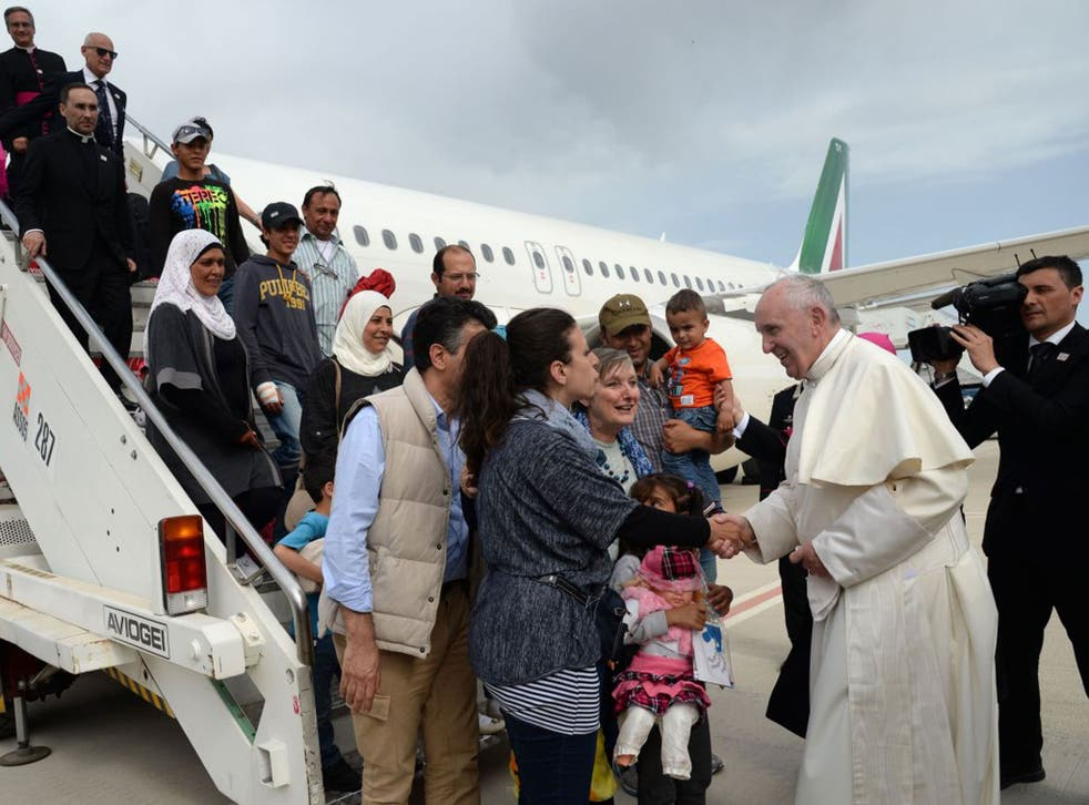 The Pope greets three refugee families who he invited to the Vatican