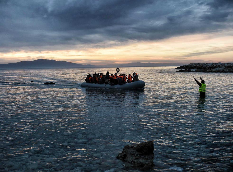 Refugees massed onto an inflatable boat reaching Mytilene, northern island of Lesbos, after crossing the Aegean sea from Turkey, on 17 February, 2016