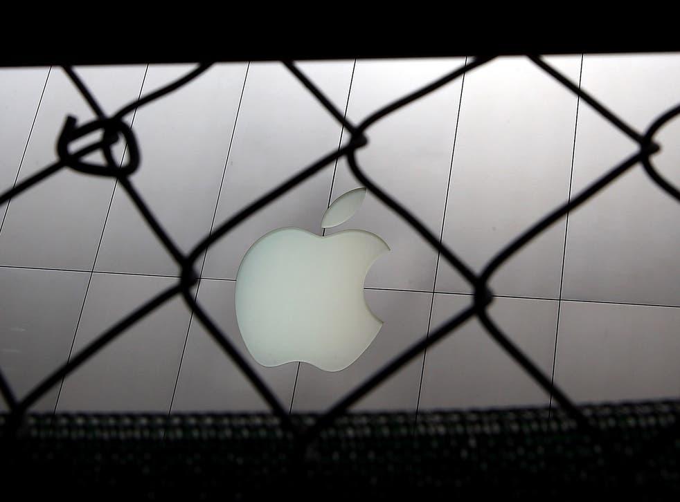 The Apple logo seen through a fence in San Francisco, California
