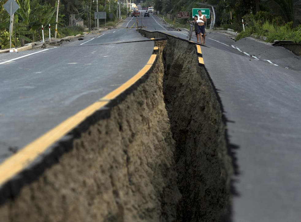 Residents look at a rift in the highway created by a 7.8-magnitude earthquake, in Chacras, Ecuador