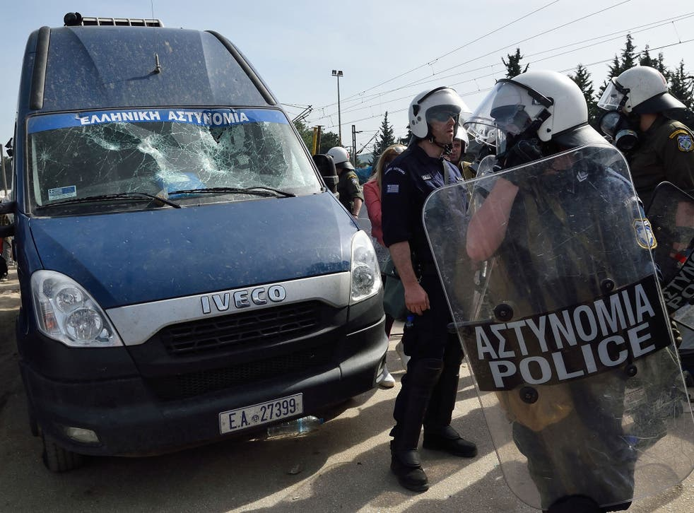 Greek police officers stand guard next to a police van that was involved in an accident that seriously injured a refugee at the Idomeni refugee camp on April 18, 2016.
