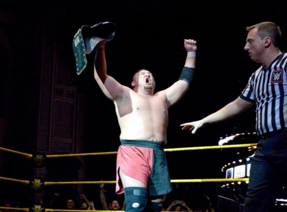 Samoa Joe lifts the NXT title after his victory over Finn Balor