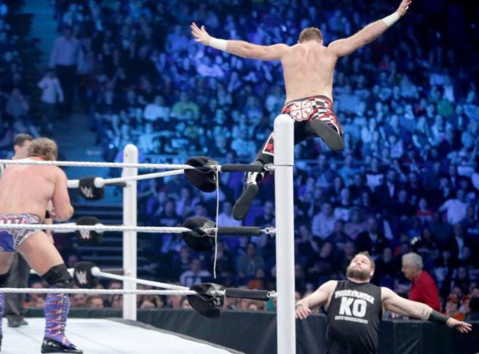 Sami Zayn leaps off the top rope to land on Kevin Owens