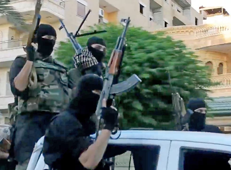 Undated propaganda video capture shows ISIS fighters riding through a town in Anbar Province, Iraq
