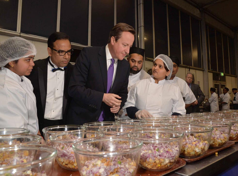 Curry Awards founder Enam Ali with Prime Minister David Cameron inspecting the winner's kitchen at the awards in 2013