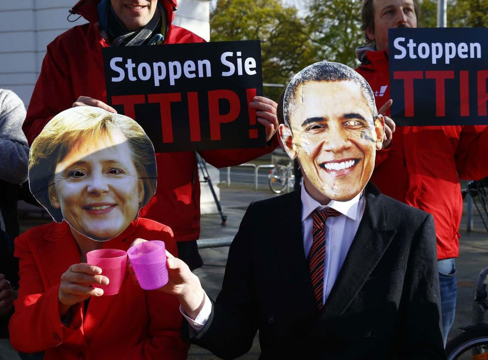 Protesters wear masks of U.S. President Barack Obama and German Chancellor Angela Merkel as they demonstrate against Transatlantic Trade and Investment Partnership (TTIP) free trade agreement before the opening ceremony of the Hannover Messe in Hanover, Germany April 24, 2016