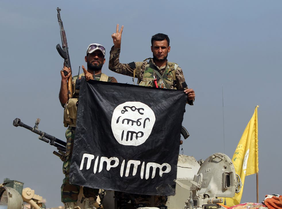 Iraqi Shiite fighters hold a captured Isis flag upside-down after an October 2015 operation