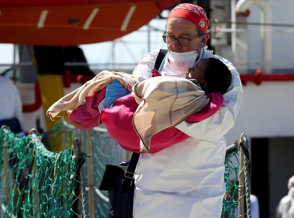 A doctor carries a child as refugees disembark from the Medecins Sans Frontieres (MSF) vessel at Pozzallo's harbour in Sicily, Italy