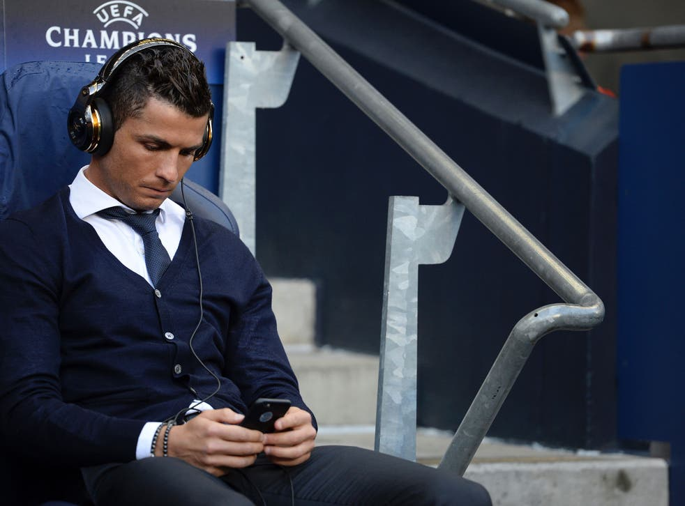 Cristiano Ronaldo on his phone before the start of the match