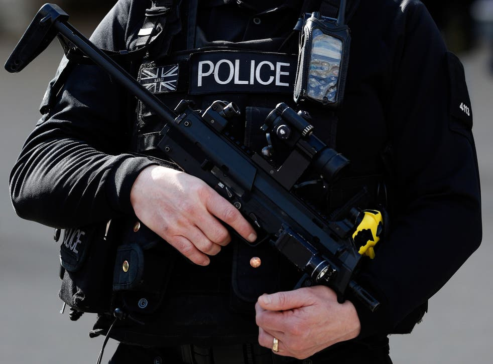 An armed British police officer holds his automatic weapon as he stands on duty in central London on March 22, 2016. B