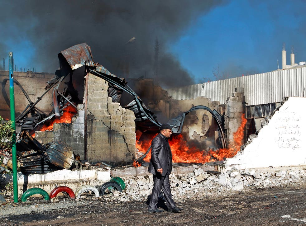 Flames rise from the ruins of a building destroyed by a Saudi air strike in Sanaa, Yemen, earlier this year