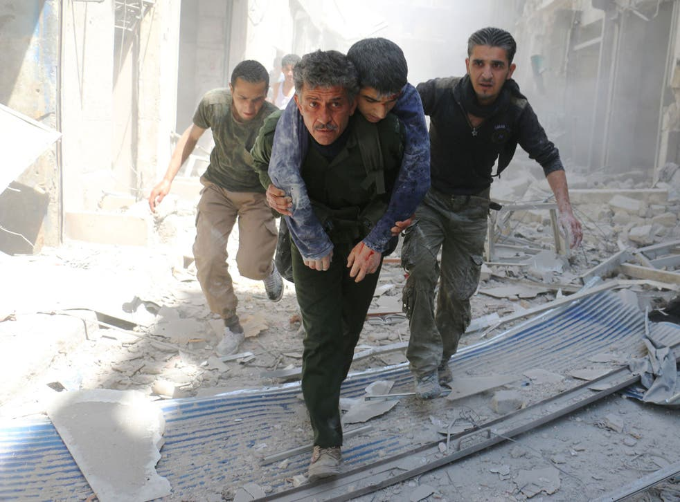 : Syrians evacuate an injured man amid the rubble of destroyed buildings following an air strike in Aleppo