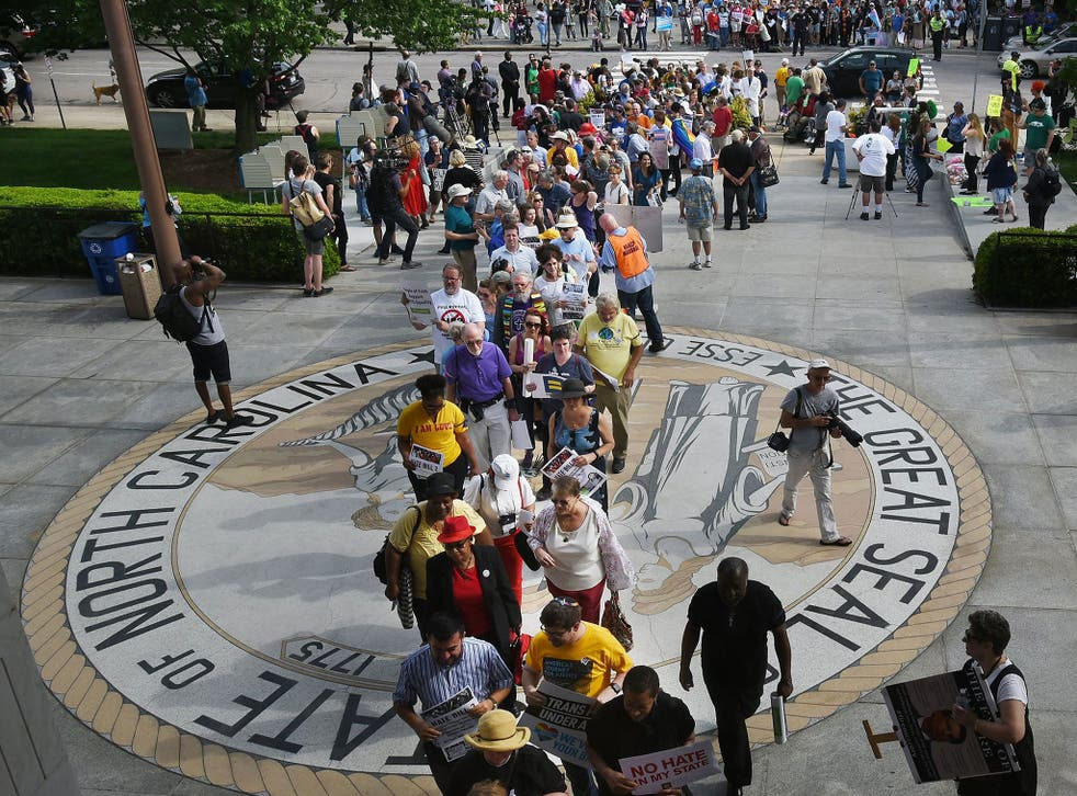 Opponents of North Carolina's HB2 walk over the state seal as they enter the legislative building for a sit-in protest in Raleigh