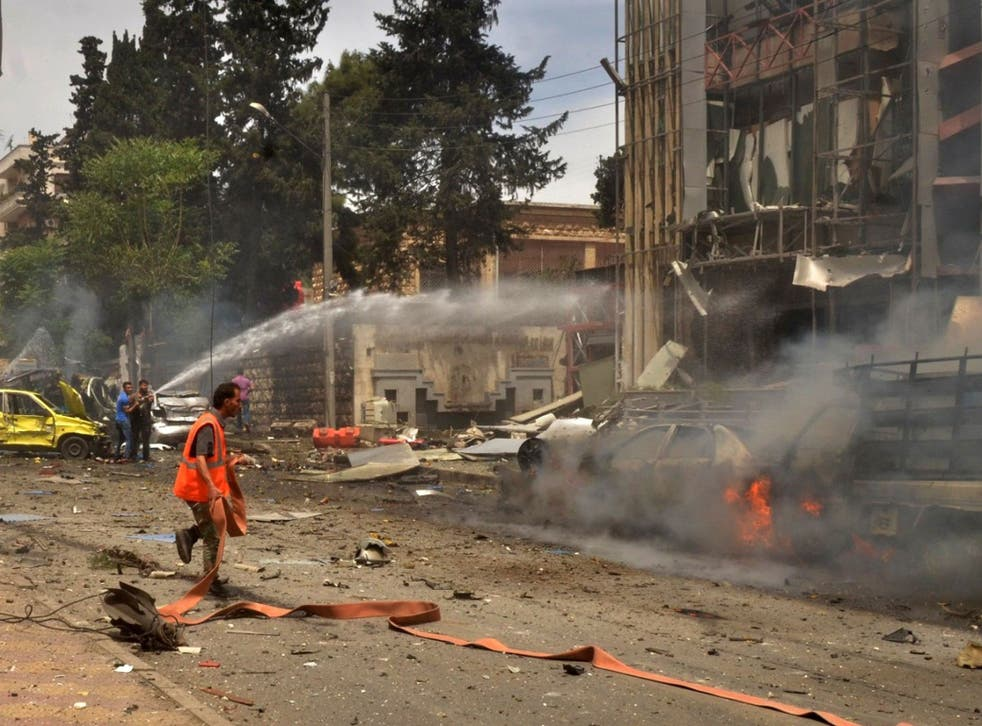 Syrian emergency personnel extinguish fires in Al-Dabbit hospital after rockets reportedly fired by rebels hit the government-controlled neighbourhood of Muhafaza in the northern city of Aleppo on May 3, 2016.