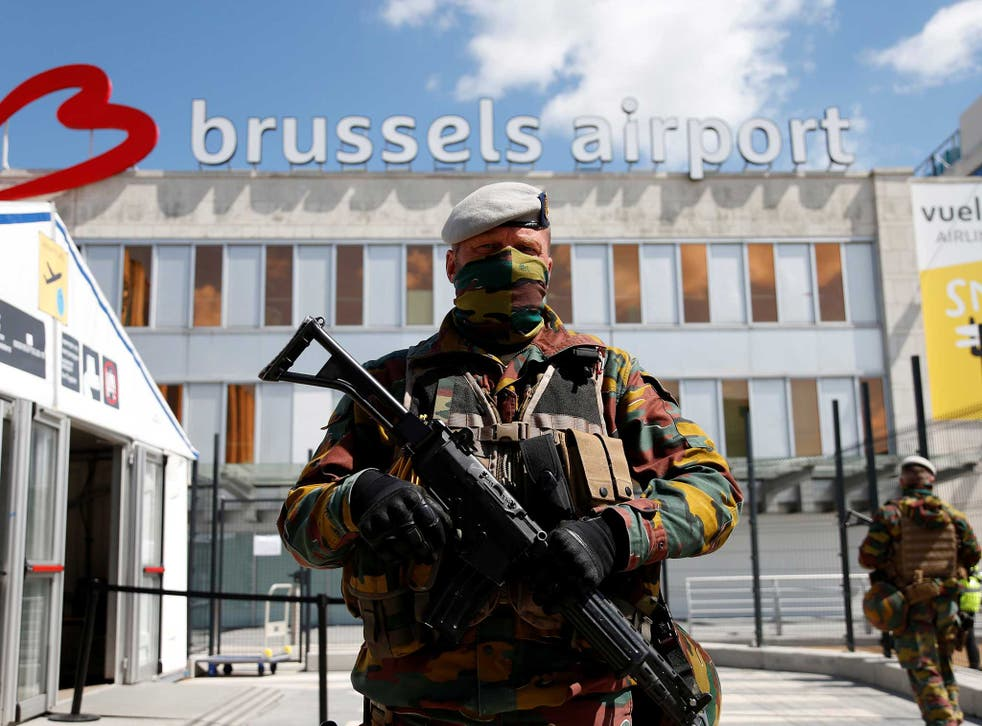 A Belgian soldier stands guard outside the partially reopened departure hall of Zaventem international airport near Brussels, Belgium