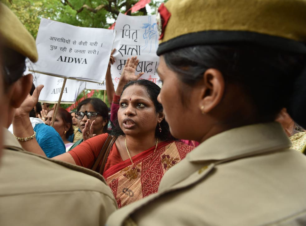 Indian activists shout slogans as they are confronted by police officials during a protest outside Kerala House in New Delhi