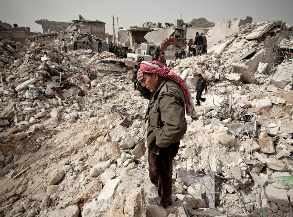 A Syrian man reacts while standing on the rubble of his house while others look for survivors and bodies in the Tariq al-Bab district of the northern city of Aleppo on 23 February, 2013