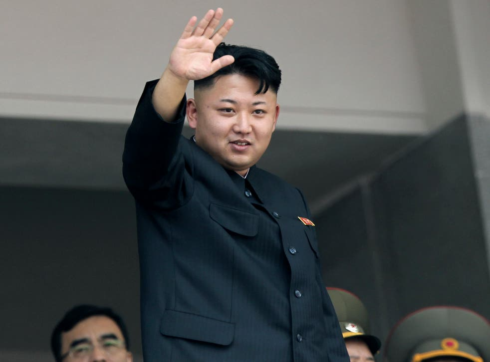 Kim Jong-un waves to spectators during a 2013 military parade