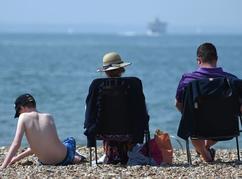 Sunbathers enjoy the warm weather on Southsea beach, Portsmouth, on May 7, 2016.