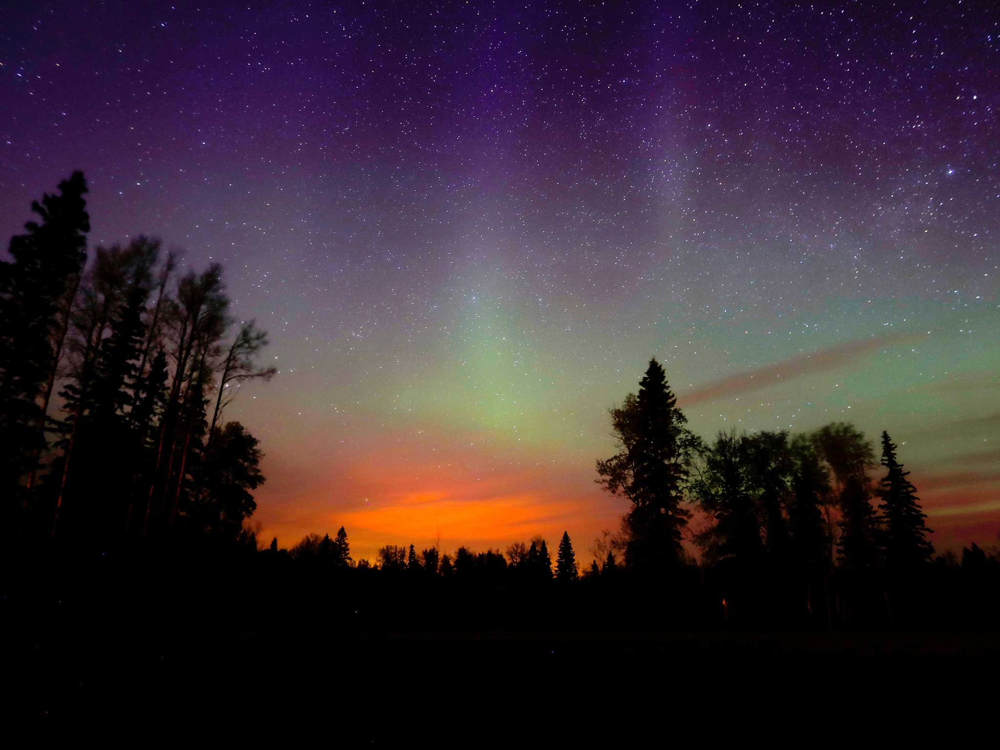 The wildfires glow underneath The Northern Lights ...