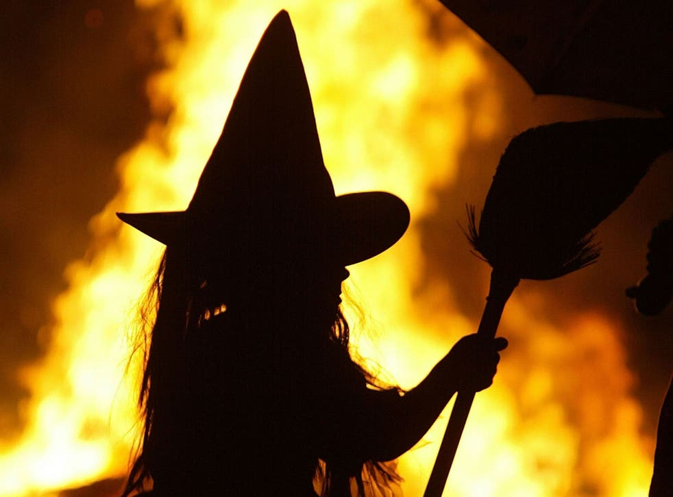A girl dressed as a witch stands by a Halloween bonfire in Maryland in 2005