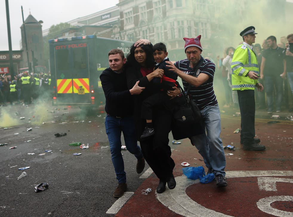 A woman and a child are helped past West Ham fans as people become violent and start throwing bottles at police outside the Boleyn Ground