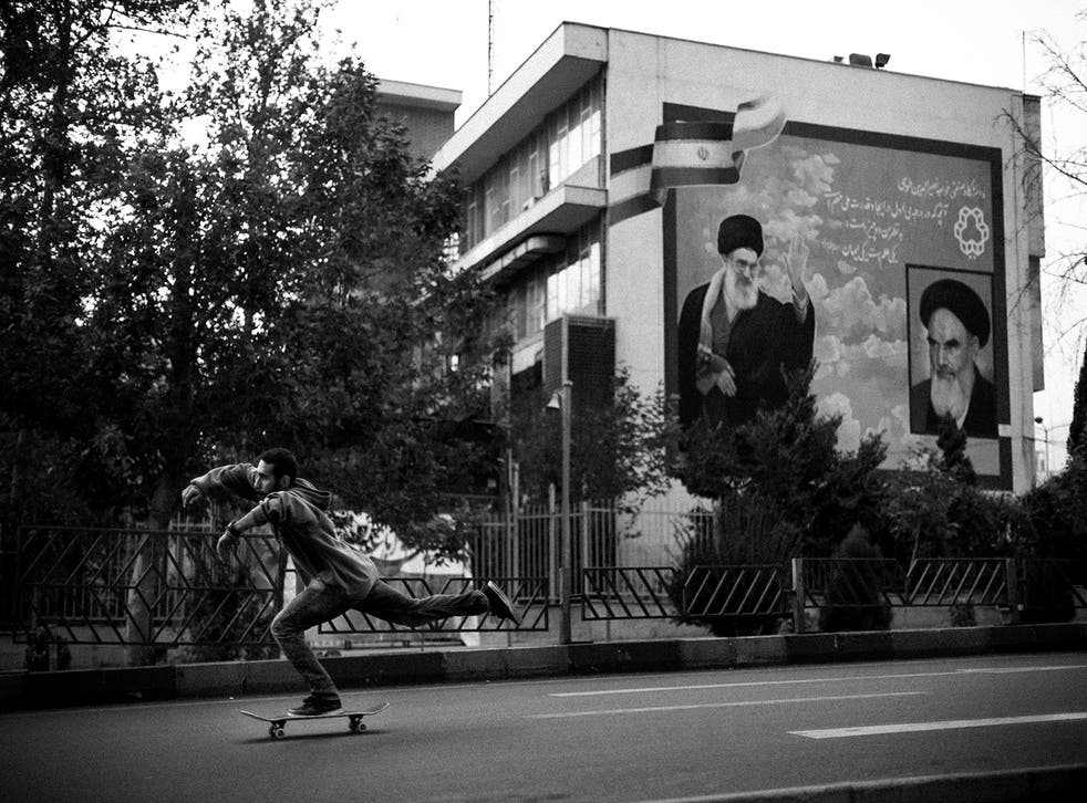 In Tehran, Erfan, 24, rides hurtles past the portraits of Khamenei (left), the Supreme Leader of the Islamic Republic of Iran since 1989, and his predecessor Khomeini (far right).