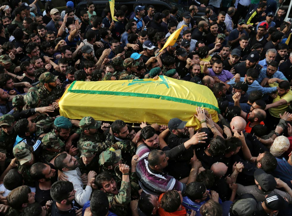 Rice is thrown by mourners ts the coffin carrying Mustafa Amine Badreddine during his funeral in a suburb of Beirut