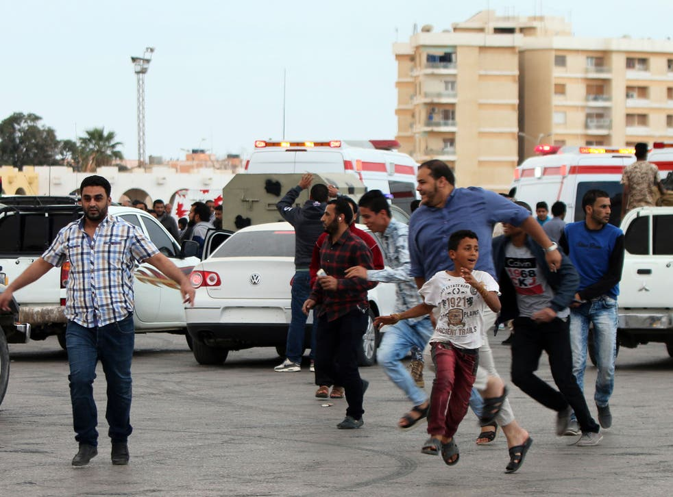 Libyans fleeing shelling at protest in Benghazi. Protesters were calling for Libyan forces to recapture the southern city of Sirte