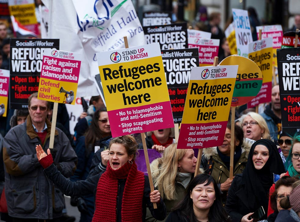 Demonstrators hold banners in support of refugees as they march through central London on March 19
