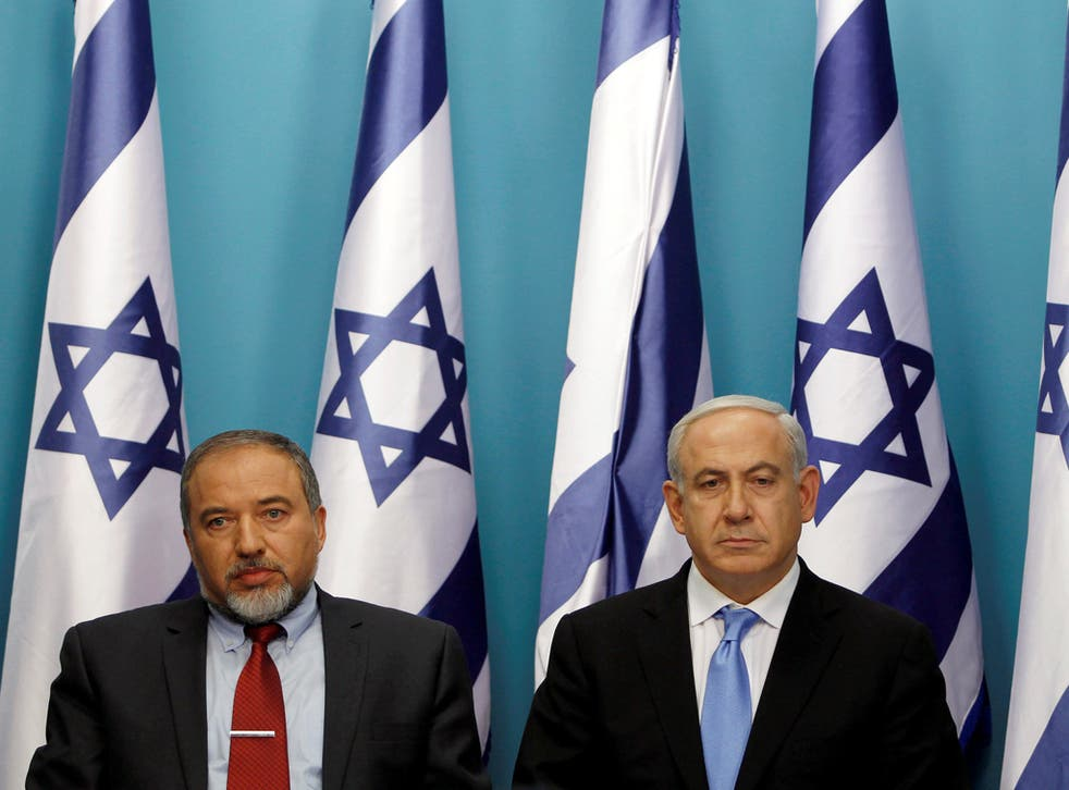 Israel's Prime Minister Benjamin Netanyahu (R) sits next to then Foreign Minister Avigdor Lieberman in 2012