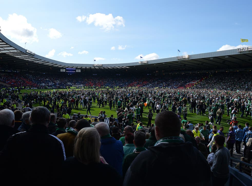 Fans invade the Hampden Park pitch after the game