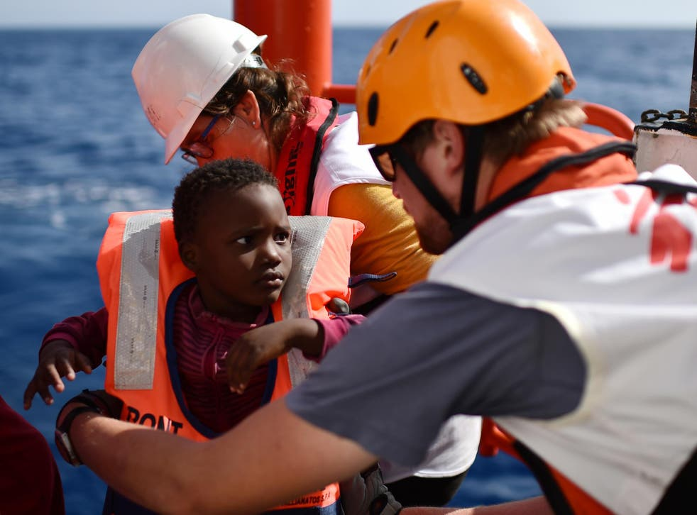 Rescuers take care of a child during a rescue operation at sea of migrants and refugees with the Aquarius, off the Libyan coast