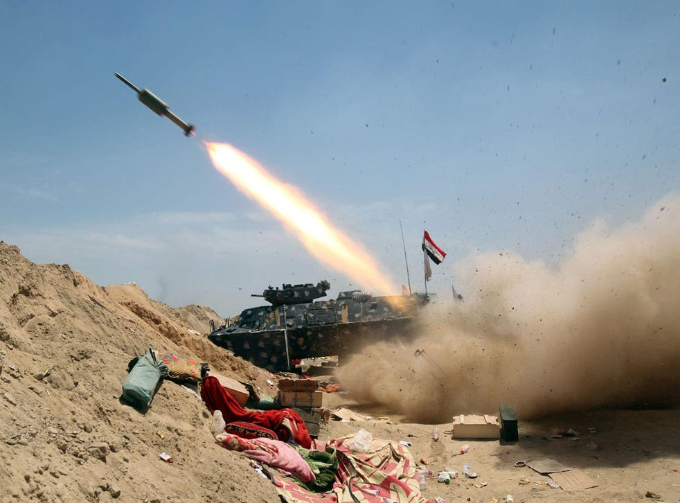Iraqi government forces fire a rocket north-east of Fallujah