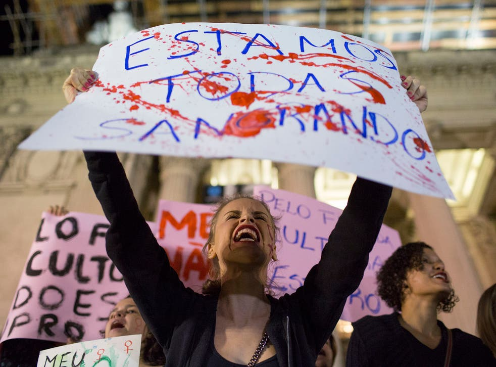 """A protester in Rio de Janeiro holding a banner that reads: """"We're all bleeding"""""""