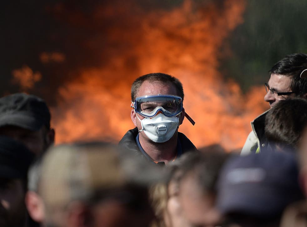 A man with a mask is pictured as workers on strike are evacuated by riot policemen as they block the access to an oil depot near the Total refinery of Donges, western france, on May 27, 2016 to protest against the government's planned labour law reforms