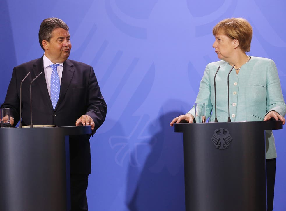 German Chancellor Angela Merkel (R) and German Economy Minister Sigmar Gabriel deliver remarks at a press conference held at the conclusion of a two-day retreat of the German cabinet in Meseberg, Germany
