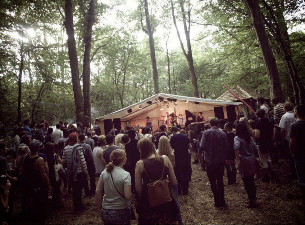Festival-goers enjoy watching a band play at In the Woods boutique festival in Kent