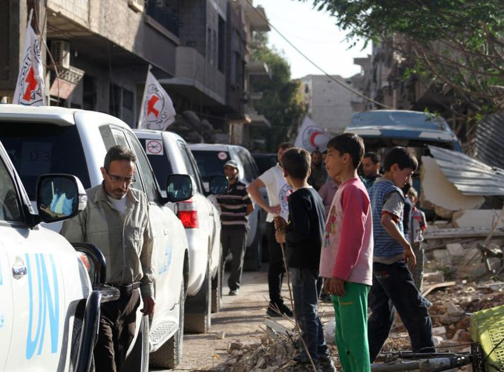 Vehicles of the International Committee of the Red Cross (ICRC), the Syrian Arab Red Crescent and the United Nations wait on a street after an aid convoy entered the rebel-held Syrian town of Daraya, southwest of the capital Damascus