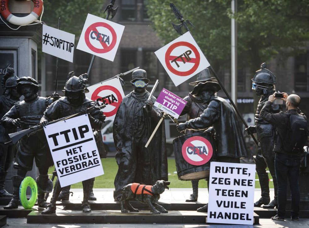 Rembrandt statues are decorated with protest signs during a demonstration against the TTIP trade agreement, in Amsterdam, last weekend