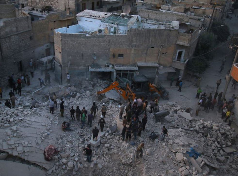 Men inspect damage after an airstrike on Aleppo